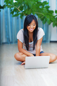 Portrait of young beautiful asian woman sitting on the floor with laptop at home