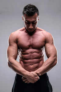 Portrait of young bodybuilder man over gray background