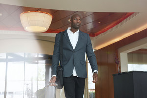 Portrait of young businessman with luggage in hotel lobby. African business executive walking in hotel hallway with his baggage.