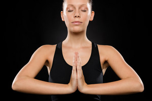 Portrait of young Caucasian woman exercising yoga with hands clasped