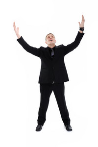 Portrait of young, happy winner businessman with arms wide open over white background
