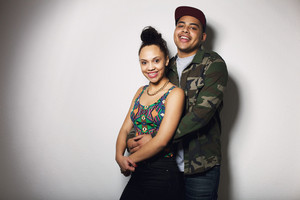 Portrait of young man and woman standing against grey background with lots of copy space. Beautiful young couple looking at camera smiling.