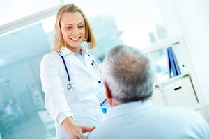 Portrait of young pretty assistant looking at mature clinician while interacting with him