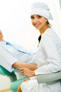 Portrait of young professional looking at camera on background of patient