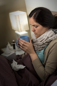 Portrait of young sick woman drinking tea suffering from cold