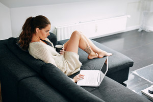 Portrait of young woman sitting on sofa checking her emails. Attractive female model with a cup of coffee and laptop at home in morning.