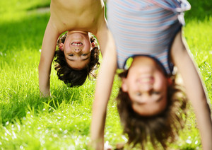 Portraits of happy kids playing upside down outdoors in summer park