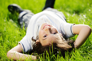 Portraits of happy kids relaxing outdoors in summer park on grass