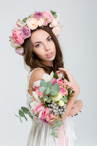 Portrat of tender charming young bride in rose wreath with bouquet of flowers isolated over white background