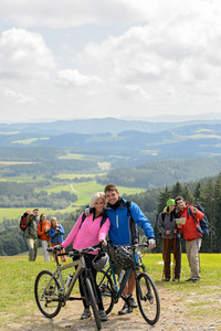 Posing cyclist couple on the mountain top with bikes