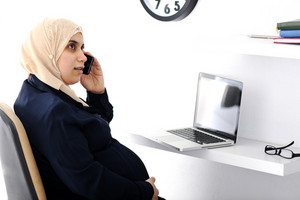 Pregnant Muslim Arabic business woman speaking on phone