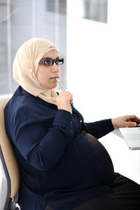 Pregnant Muslim Arabic business woman working at office