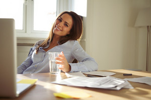 Pretty businesswoman sitting at her desk with a glass of water looking at camera smiling. Confident young caucasian woman working from home office.