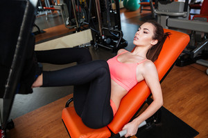 Pretty concentrated young sportswoman doing exercises for legs using gym equipment