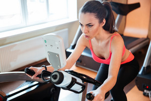Pretty concentrated young woman athlete working out on bicycle in gym