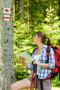 Pretty female hiker checking the map and blaze