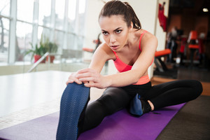 Pretty focused young woman athlete stretching legs on yoga mat in gym