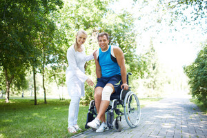 Pretty nurse and male patient in a wheelchair looking at camera in park