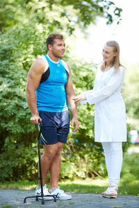 Pretty nurse looking at male patient trying to walk on his own in park