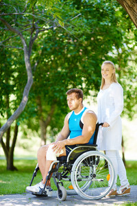 Pretty nurse walking with male patient in a wheelchair