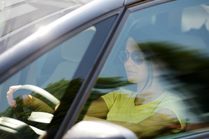Pretty woman driving a car, mysterious look behind the glass
