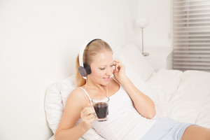 Pretty woman listening to music and drinking coffe