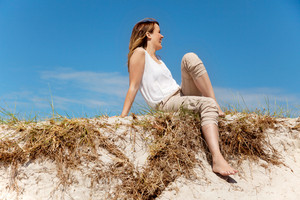 Pretty woman sitting on sand dune against the bright sky background
