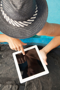 Pretty woman using a tablet in the edge of the  pool