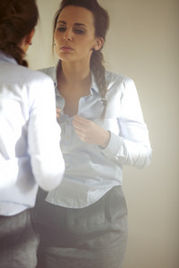Pretty young business woman buttoning up her shirt in front of mirror. Caucasian female model getting dressed for office at home.