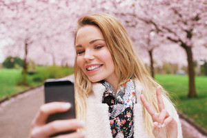 Pretty young female model gesturing peace sign while taking her picture with cell phone. Beautiful caucasian young woman taking self portrait while at spring blossom park.