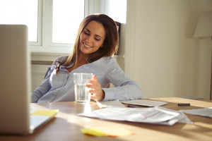Pretty young  sitting at her desk looking at glass of water thinking. Beautiful young businesswoman at home. Female working from home office.