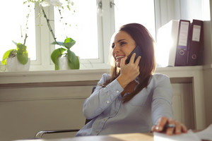 Pretty young woman talking on mobile phone while sitting at her desk. Beautiful businesswoman working from home office.