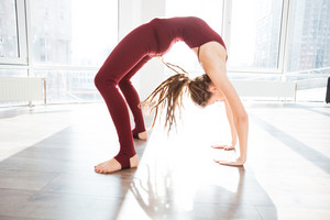 Pretty young woman with dreadlocks doing exercises and bending in yoga studio