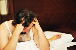 Problems in bed, unhappy husband siting beside his wife