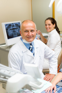 Professional dental surgeon sitting in office with assistant nurse