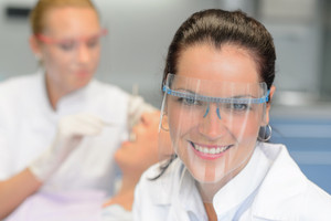 Professional dentist with protective glasses patient woman dental checkup