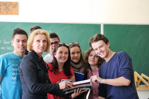 Professor and a student surrounded by a group of students holding a copybook