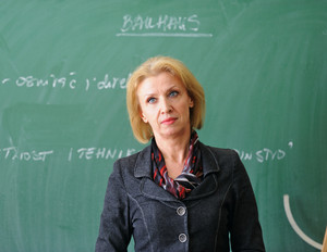Professor standing in front of a blackboard giving a lecture