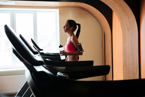 Profile of attractive serious young sportswoman walking on treadmill and drinking water in gym