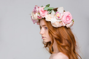 Profile of attractive young woman with wavy red hair in beautiful flower wreath over grey background