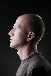Profile of white bald man in his twenties in dark