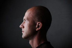 Profile of white bald man in his twenties in dark