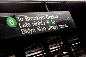 Public New York City subway sign pointing to the Brooklyn Bridge.