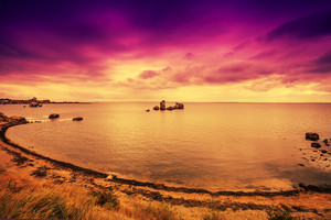 Purple sunset over beach with dramatic sky