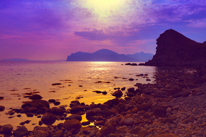 Purple sunset over rocky beach