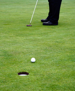 Putting A Golf Ball On The Putting Green