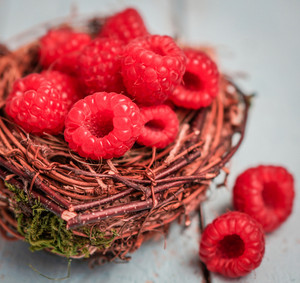 Raspberries In The Basket On Wooden Background