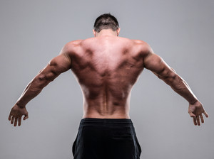Rear view of a muscular man over gray background