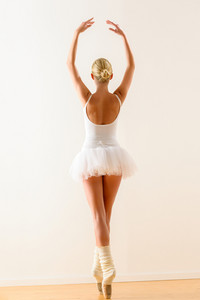 Rear view of ballerina standing on tiptoe with raised arms