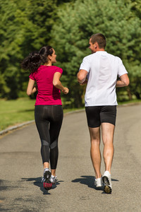 Rear view of couple friends jogging together outdoors